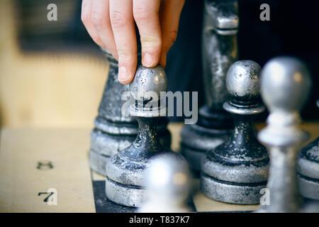 Sulla scheda ci sono vecchi shabby grandi pezzi di scacchi e il giocatore effettua una decisione difficile