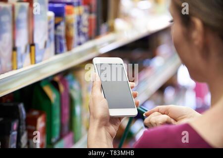 Close Up di lettura Donna Shopping List dal telefono cellulare Foto Stock