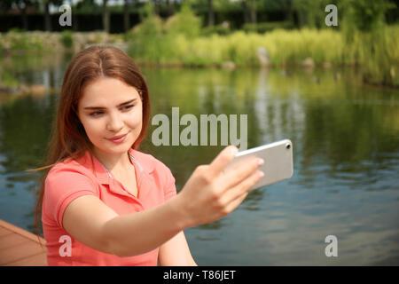 Giovane donna prendendo selfie vicino al fiume Foto Stock