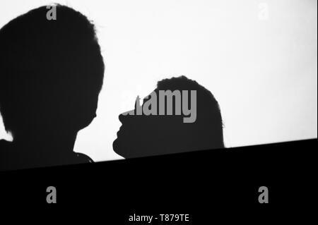 Sfondo astratto ombre di persone un uomo e una donna matura, sulla parete digitale luce dal proiettore cinematografico sulla parete di una immagine in bianco e nero