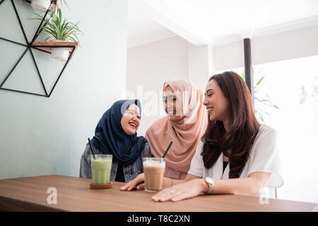 Asian donna musulmana migliori amici insieme in cafe Foto Stock