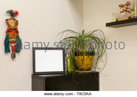 Vuoto orizzontale nero picture frame su un ripiano con una coda di cavallo palm e una maschera tribale. Per irridere le foto e illustrazioni. Foto Stock