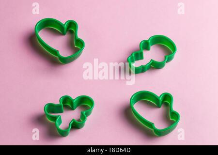 Verde di natale cookie cutters sulla rosa table.anno nuovo. vacanze, utile strumento per chef. top view foto Foto Stock