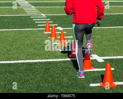 Una scuola di atleta femminile esegue trapani in esecuzione su coni arancione su un tappeto erboso verde campo su un luminoso rientrano nel pomeriggio grigio indossa spandex. Foto Stock