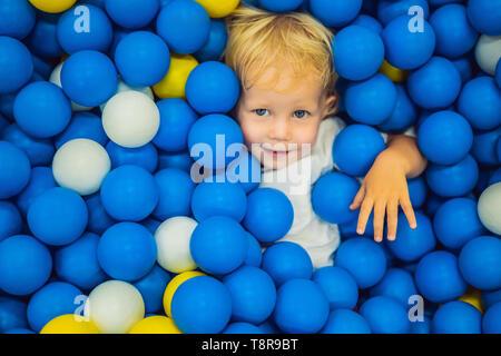 Bambino che gioca palla in buca. Giocattoli colorati per i bambini. Asilo nido o alla scuola materna sala da gioco. Il Toddler kid a cura di giorno del parco giochi al coperto. Palline per piscina