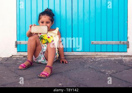 Bambina prende un selfie con la smart-phone di fronte ad una porta blu, ragazza godendo con la tecnologia in vacanza Foto Stock