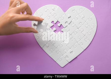 Donna facendo puzzle sul colore di sfondo Foto Stock