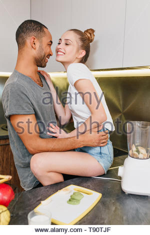 Amanti in t-shirt sorridente, flirtare in cucina, un intimo momento. Paio di guardare tutti gli altri con la passione e l'amore. Il marito abbraccia la moglie in pantaloncini corti. Foto Stock