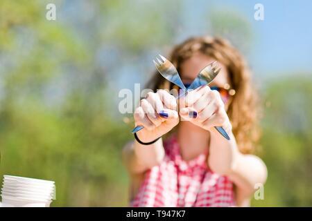 Teen di età ragazza in rosso a scacchi shirt seduti a tavola sul compleanno party in giardino - incrocio forche Foto Stock