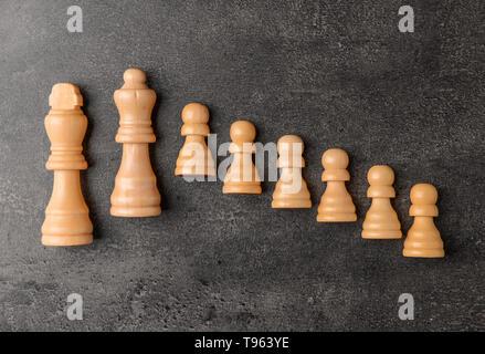 Pezzi di scacchi su sfondo grigio Foto Stock