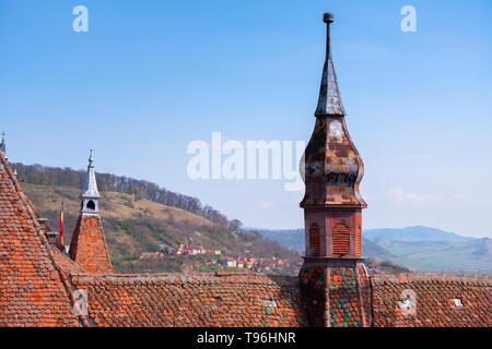 Dettagli del tetto della chiesa del monastero domenicano in Sighisoara in una giornata di sole in primavera. I boschi della Transilvania in background
