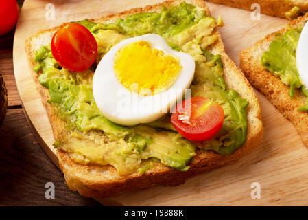 Sandwich con avocado, uova in camicia e pane integrale sul bordo di taglio Foto Stock