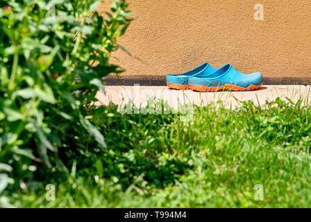 Una coppia di colorati scarpe da giardinaggio è in piedi nel sole luminoso su alcune pietre sul marciapiede davanti a un muro di casa nel giardino con qualche erba Foto Stock