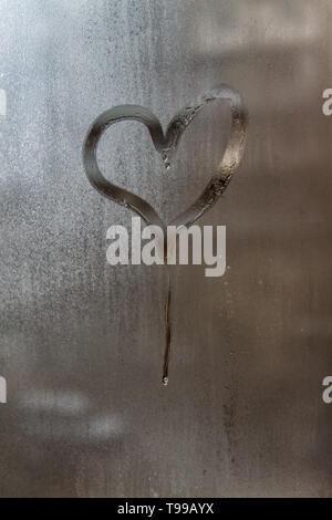 Sgocciolare in forma di cuore su una finestra atomizzata-vetro. Close-up. Sfondo. Foto Stock