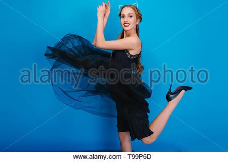 Slim girl dancing a parte la sua graziosa dress svolazzanti e lei ha una gamba verso l'alto. Indossare nero elegante scarpe con i tacchi alti, diadema con cat le orecchie e diamanti. In posa su sfondo blu. Foto Stock