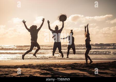 Tramonto sulla spiaggia con felice del gruppo di giovani persone che saltano divertendosi - amici su vacanze estate vacanze godendo insieme in amicizia - sandy l Foto Stock