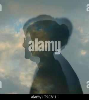 Profilo del giovane ragazza all'interno di un profilo di donna anziana contro un cielo nuvoloso raffigurante il passare del tempo e invecchiamento Foto Stock