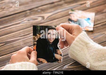 Donna che mantiene parte lacerata della foto con il suo ex marito. Concetto di divorzio Foto Stock