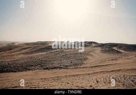 Auto superare le dune di sabbia di ostacoli. Concorrenza racing sfida deserto. Unità auto offroad con nuvole di polvere. Veicolo Offroad racing ostacoli in wi Foto Stock