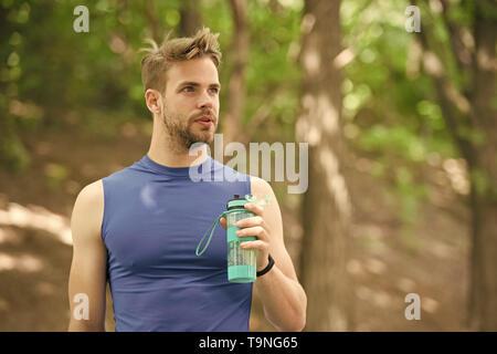 Ad appena un minuto di riposo. Uomo aspetto atletico detiene una bottiglia con acqua. L'uomo atleta nello sport vestiti si preoccupa per il bilancio idrico. Lo sport e la vita sana Foto Stock