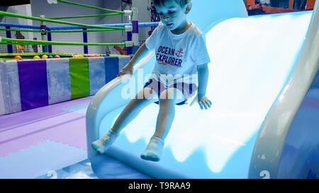 Ritratto di poco il toddler boy a cavallo sul illuminate scorrere sul palyground presso il parco di divertimenti Foto Stock