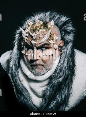Gravi imperatore di perpetua realm freddo indossando white pelliccia con cappuccio. Demone con corna sulla testa e golden pelle splendente isolati su sfondo nero Foto Stock