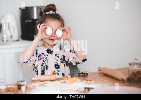 Sorridente ragazza di capretto 4-5 anno vecchio divertendosi con uova crude in cucina. Rendendo i cookie in ambienti chiusi. Infanzia. Foto Stock