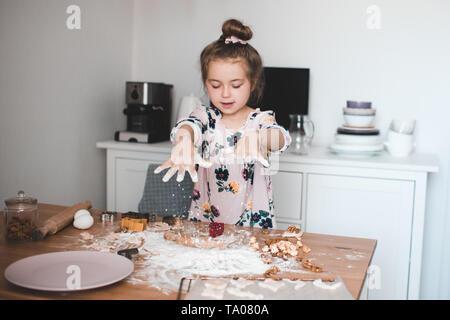 Carino Baby girl 4-5 anni di giocare con la farina e la pasta in cucina closeup. La cottura di bambino in ambienti chiusi. Foto Stock