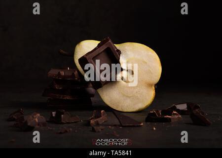 Pera e cioccolato su sfondo di legno, stato d'animo scuro Foto Stock