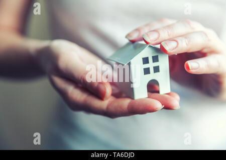 Donna femmina mani piccole bianco in miniatura toy house. Ipoteca assicurazione immobiliare sogno casa mobile e immobiliare di concetto Foto Stock