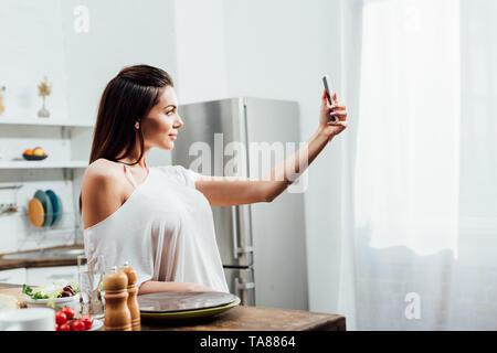 Affascinante giovane donna prendendo selfie vicino a tavola in cucina Foto Stock