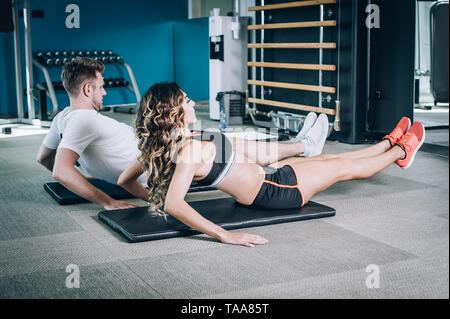 Attraente muscolare fitness sorridente donna con pulmann facendo hard esercizio in palestra moderna. Power fitness, sport, formazione, lo stile di vita Foto Stock
