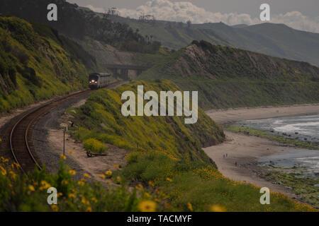 Passeggero Surfliner express treno corre sui binari della ferrovia lungo la scogliera accanto all'Oceano Pacifico in Santa Barbara County, California, Stati Uniti d'America