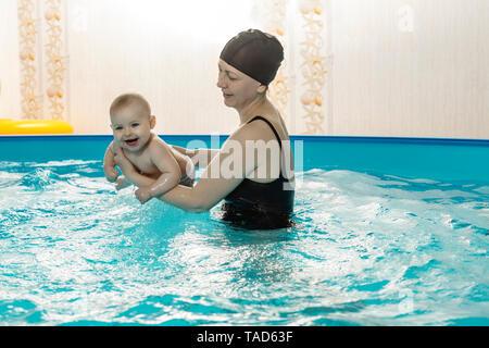 Baby nuoto, madre e figlia in piscina Foto Stock