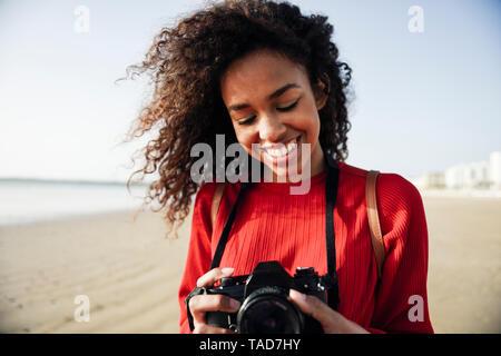 Sorridente giovane donna che guarda la fotocamera sulla spiaggia