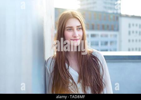 Ritratto di sorridente giovane donna appoggiata contro una parete Foto Stock