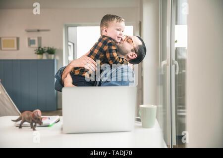 Padre seduta a tavola in casa ufficio abbracciando il figlio Foto Stock