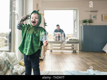 Felice ragazzo in un costume a giocare con il personaggio giocattolo a casa Foto Stock