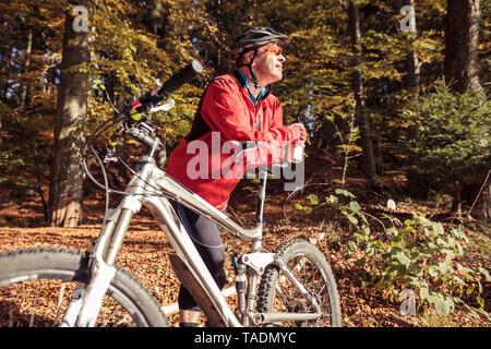 Uomo con mountainbike avente una pausa nella foresta Foto Stock