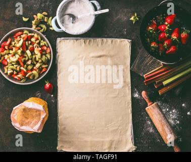 Foglio di pasta su una cucina rustica tabella con il rabarbaro e le fragole ingredienti per lo strudel torta, vista dall'alto. Cottura stagionali. Alimenti biologici. Fase Foto Stock