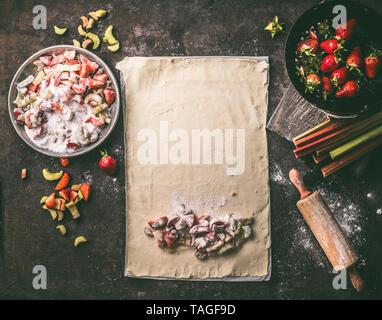 Foglio di pasta con dadini di rabarbaro e fragole ingredienti per lo strudel torta rustica sul tavolo da cucina, vista dall'alto. Cottura stagionali. Alimenti biologici. Fase Foto Stock