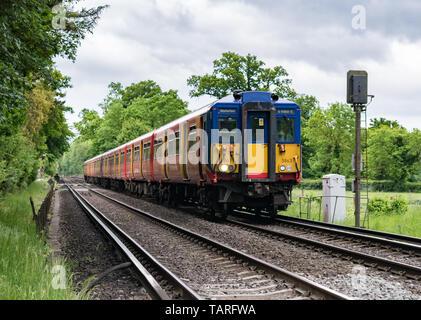 Un treno di onde di driver come la sua classe 455 South Western Railway passenger service treno passa un segnale in la campagna del Surrey, voce di Waterloo.