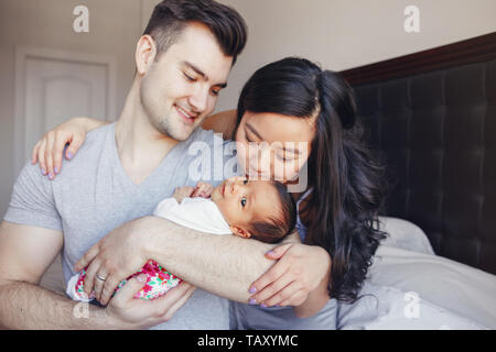 Ritratto di bella sorridente padre caucasici e asiatici cinese madre baciare razza mista Neonato Bimbo figlio figlia. La famiglia felice in camera da letto. Foto Stock