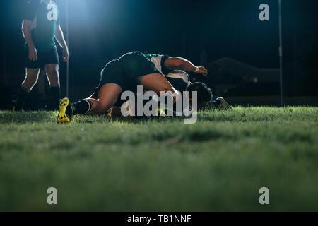 Forti giocatori di rugby in lotta per la sfera durante il gioco a Stadium. Rugby sforzandosi per la palla in gioco di notte su sport arena. Foto Stock
