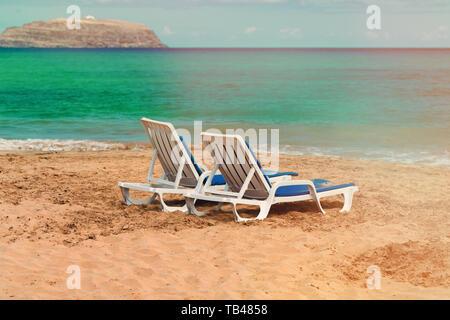Vuoto due sedie a sdraio su una deserta spiaggia sabbiosa sull'oceano. Foto Stock