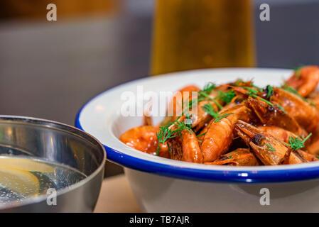 Preparate i gamberetti con aneto nella ciotola sul tavolo con due bicchieri di birra e acqua
