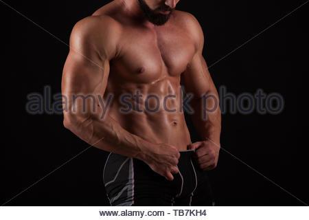 Bello muscoloso bodybuilder che posano su sfondo nero Foto Stock