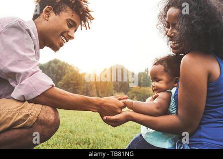 Felice famiglia africana godendo del tempo insieme nel parco pubblico - il padre e la madre per divertirsi giocando con la loro figlia al tramonto per esterno Foto Stock