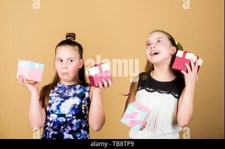 Felici i bambini amano regali di compleanno. Shopping e vacanze. Sorelle godere presenta. I bambini tenere confezioni regalo sfondo beige. Oh Happy day. I ragazzi ragazze felici dono. Ragazze adorabili e festeggiare il compleanno. Foto Stock
