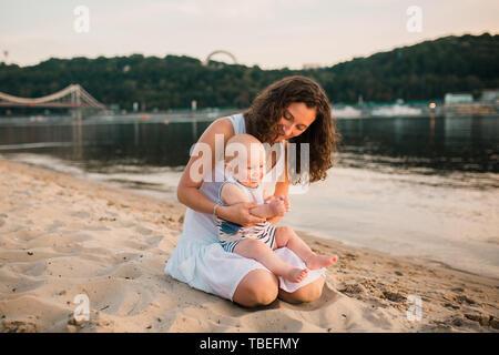Madre giovane seduto sulla spiaggia con un anno di età baby figlio. Ragazzo che abbraccia, sorridente, ridere, giorno d'estate. Infanzia felice spensierato gioco all'aperto Foto Stock